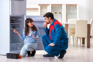 Man repairing fridge with customer