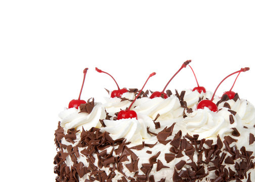 Close up on a black forest cake isolated on a white background. Whipped cream, shaved chocolate candy, cherries on top.