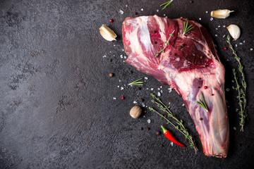 Raw fresh Lamb Meat shank and seasonings on black stone background