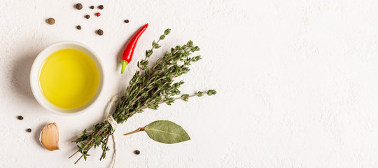 Olive oil and bouquet of thyme on a white stone background