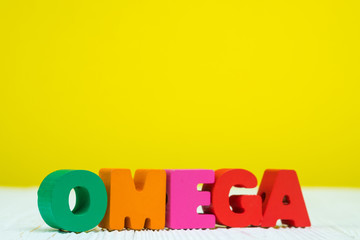 OMEGA text alphabet on white wooden table yellow wall background with copy space.