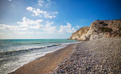 Wall Mural - Beautiful scenery, a stone pebble beach, blue sea waves and rocks, a trip to Cyprus