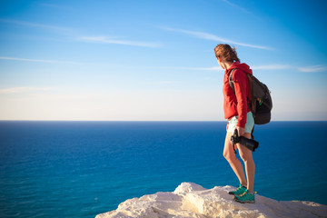 Young professional photographer woman stands with photo camera in hands on rock above the sea, beautiful nature, profession, vacation and travel concept