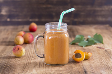 Healthy eating, food, dieting and vegetarian concept - smoothie from apricot and peach in glass mug. Fresh apricot and juice on wooden background