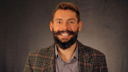Bearded guy with a beautiful smile looks at the camera
