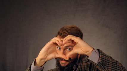 A bearded guy shows his heart in the camera.
