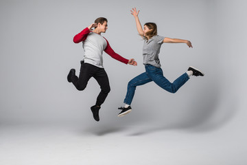 He vs She. Full length portrait of attractive, playful, cheerful, comic couple in casual outfit, jeans, shirts jumping over grey background