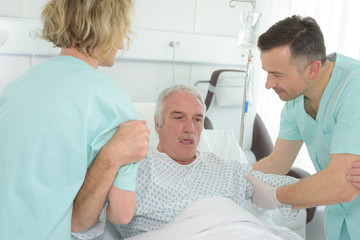 older man lying in hospital bed with nurses helping him