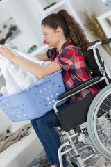 girl on wheelchair folding clothes
