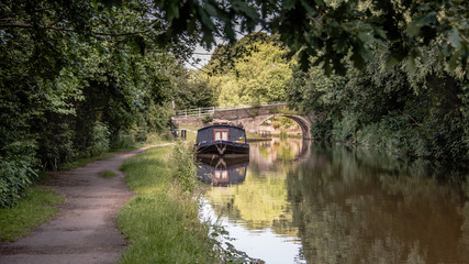 A peaceful scene looking down a canal towpath. There is a narrow boat moored up in front of an old road bridge crossing the water.. The scene is set in between trees at the side of the canal