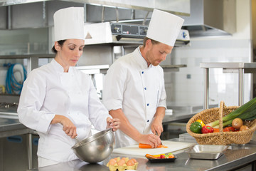 man and woman chefs cooking food at restaurants kitchen