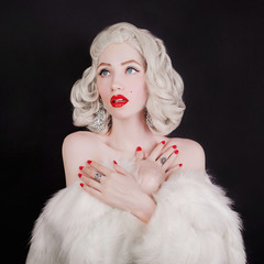 Marvelous blonde woman with birthmark on face in white fur coat on black background. Portrait of young pale girl with white hair. Beautiful woman with earrings on ears. Marvelous model with red nails