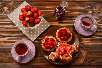 Tea drinking with tartlets and cakes with strawberries