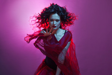 Dancing woman with flying red dress. Beautiful Gothic girl like a witch
