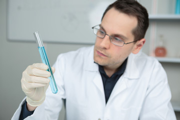 Male scientist looking at test tube containing blue liquid