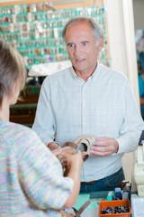 Cobbler conversing with customer