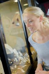 pretty blonde woman looking at jewellery window