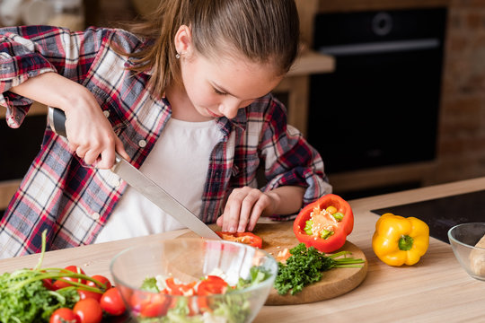 little cook. adolescent girl cutting vegetables and preparing dinner from fresh organic food ingredients. healthy eating and wholesome nutrition concept.