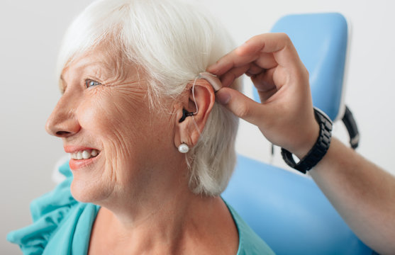 doctor helping senior patient with hearing aid , close-up