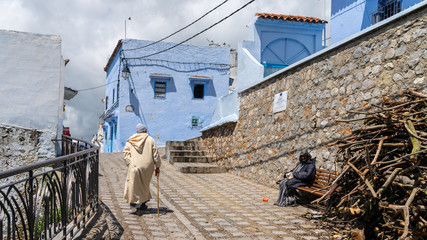 Unidentified man walking in blue medina of Chefchaouen city in Morocco, North Africa