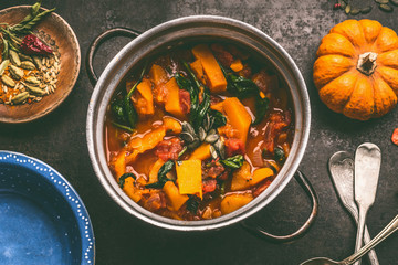 Close up of tasty pumpkin dish in cooking pot on dark rustic kitchen table background, top view. Pumpkin stew.   Autumn seasonal rustic country food