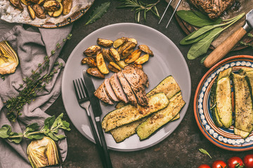 Plate with grilled pork steak,   roast and fresh vegetables and baked potatoes, plates and cutlery on rustic wooden table, top view. Rustic food