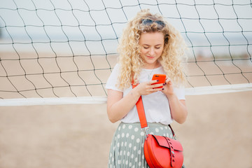 Oudoor shot of pleasant looking blonde female holds cell phone, shares photos in social networks, dressed casually, uses free internet, has walk across beach, stands near tennis net. Technology