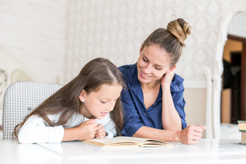 happy family mother and daughter read a book in the evening at home. the concept of family comfort and family relations