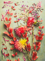 Wall Mural - Autumn flowers and leaves flat lay composing, top view. Fall floral still life with chrysanthemums and red orange branches.