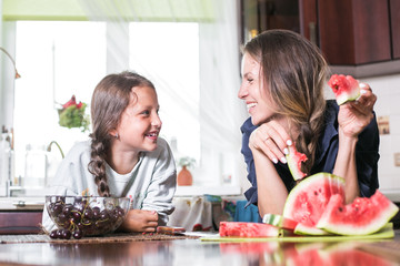 Cute little girl and her beautiful mom are cutting fruits, red watermelon and smiling while cooking in kitchen at home. Happy Family