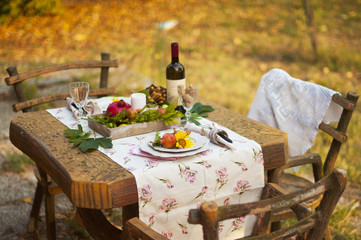Romantic dinner in the autumn garden, table setting for a nice dinner. Wine, fruit, pomegranate and flowers. Picnic in the open air