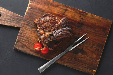 Rib eye steak on wooden board, top view