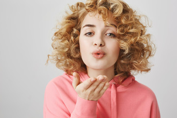 Mwah for all my besties. Portrait of good-looking cute curly-haired girl puckering with lovely expression and holding palm near lips to blow kiss at camera, standing over gray background