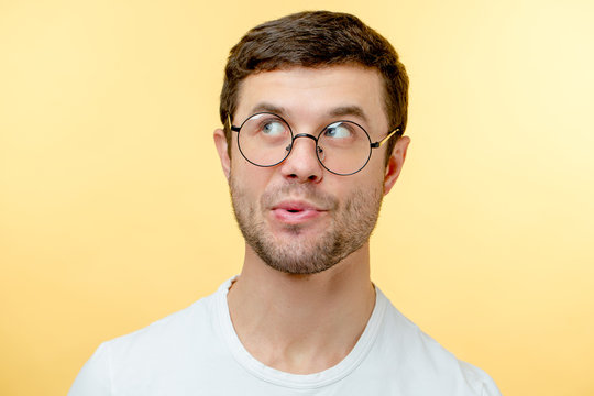 pleasant young man in glasses whistling a song. guy with interesting expression. look up. indifference concept