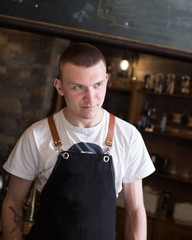 Portrait of young handsome man wearing a black apron standing in a coffee shop.profession concept