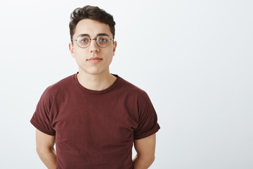 Waist-up shot of creative smart european boyfriend in red t-shirt, holding hands behind chest, wearing glasses, staring focused at camera, waiting for commands or orders, standing serious