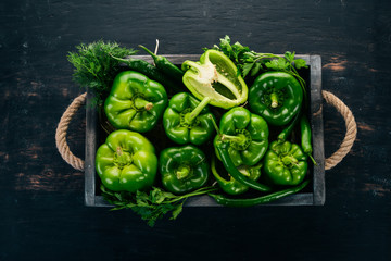 Fresh green pepper in a wooden box. Organic food. Top view. Free space for text. Wall mural