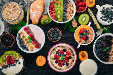 Oatmeal with yogurt, fruits and berries in plates. Breakfast. On a black wooden background. Top view. Free space for text.