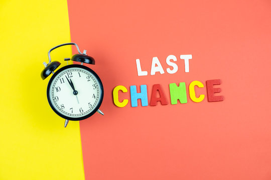 Top view of last chance wording and alarm clock on colorful background