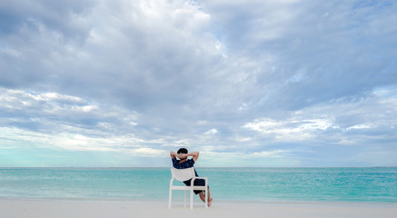 Summer concept , A man relax sit on white chair on the beach white sand and turquoise sea color at maldives on the weekend holidays