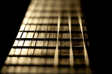 Concert music instrument guitar strings in golden musician style. Closeup of the string instrument for classic rock pop isolated on black background