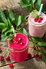 Raspberry and Cherry milkshake or smoothie on a dark wooden table. Healthy juicy vitamin drink diet or vegan food concept.
