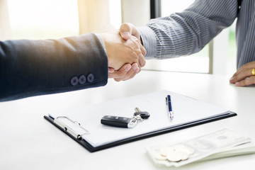 Businessman giving end key to customer after good deal agreement. while loan agreement being approved and calculator, Buy house concept.