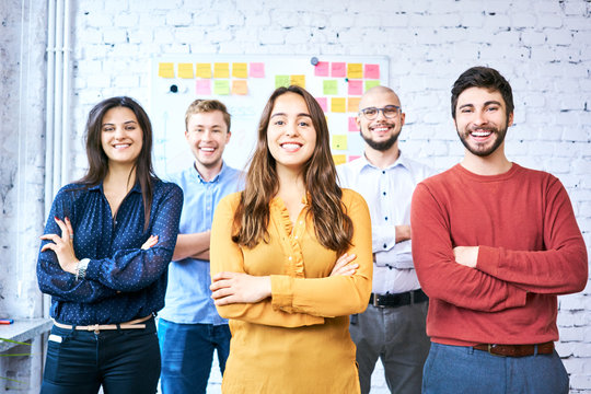 Cheerful students looking at camera with arms crossed. Group of startup entrepreneurs in modern office