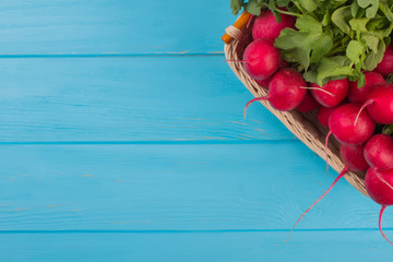Wicked basket with reddish and blue wooden background. Close up. Vegetables and copyspace.