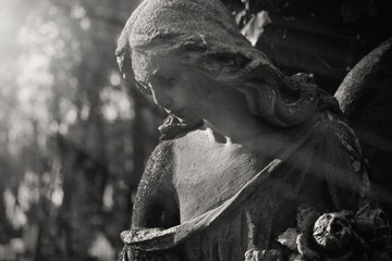 Beautiful sad angel. Vintage styled image of ancient statue. Fragment of sculpture. (religion, faith, death, resurrection, eternity concept)
