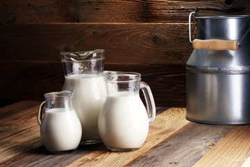 A jug of milk and glass of milk on a wooden table