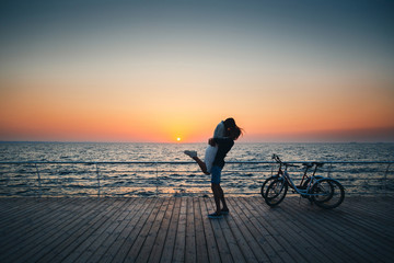 Man holding his girlfriend, couple of young lovers kissing at the beach at sunrise sky at wooden deck summer time