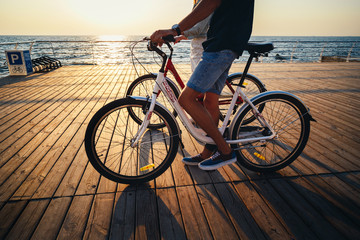 Close up of couple of young hipsters cycling together at the beach at sunrise sky at wooden deck summer time