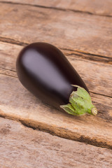 Purple ripe raw eggplant on wood. Close up. Old vintage rustic wooden background.